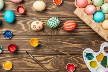 Photo for Top view of painted easter eggs, color palette and acrylic paints on wooden surface - Royalty Free Image