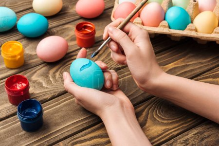 Photo for Cropped view of woman decorating easter eggs with paintbrush at wooden table - Royalty Free Image