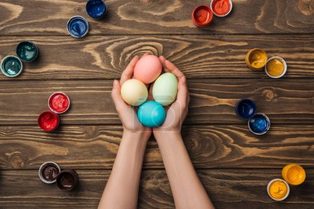 Photo for Top view of woman holding pastel easter eggs on wooden surface with paints - Royalty Free Image