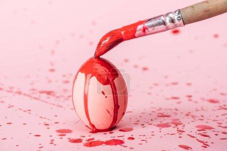 Photo pour Oeuf de Pâques avec les flaques de peinture rouge et pinceau rose - image libre de droit