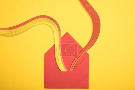 top view of opened red envelope with rainbow on yellow background