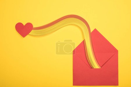 Photo for Top view of open red envelope with rainbow and heart sign on yellow background - Royalty Free Image