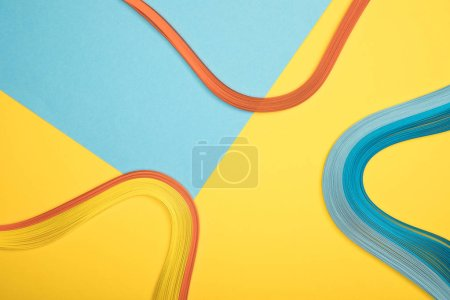 Foto de Vista superior de líneas curvas multicolores sobre fondo azul y amarillo - Imagen libre de derechos
