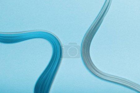 Foto de Vista superior de azul curvado líneas papel abstracto sobre fondo azul - Imagen libre de derechos