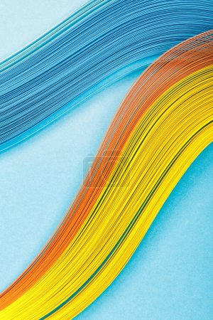 top view of yellow, orange and blue abstract lines on blue background