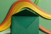 """Постер, картина, фотообои """"вид сверху разноцветные абстрактные линии на зеленом фоне с зеленым открыт конверт"""""""