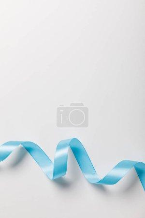 Photo pour Vue de dessus du ruban de satin ondulé bleu sur fond gris avec espace copie - image libre de droit