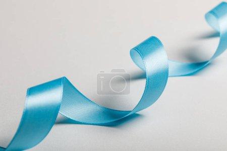 Photo pour Gros plan de ruban de satin bleu courbé sur fond gris - image libre de droit