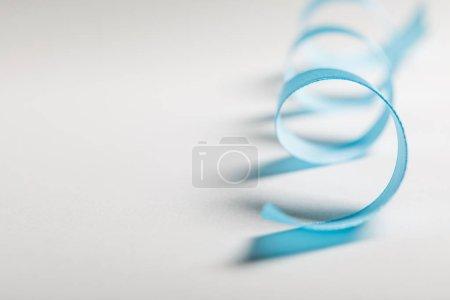 Photo pour Gros plan des courbe ruban de satin bleu sur fond gris avec espace copie - image libre de droit