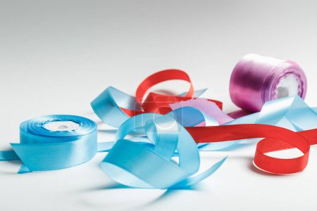 Photo for Curved blue, red and purple satin ribbons with spools on grey background - Royalty Free Image