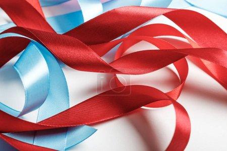 Foto de Curva de cintas de raso azules y rojos sobre fondo gris - Imagen libre de derechos