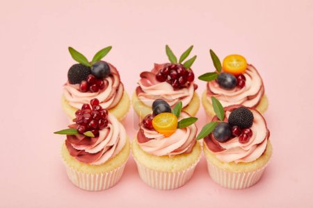 Photo for Sweet cupcakes with fruits and berries on pink surface - Royalty Free Image