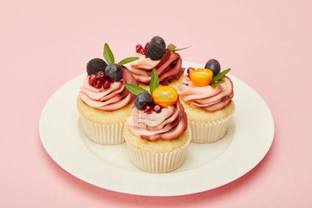 Photo for Sweet cupcakes with berries and fruits on plate on pink surface - Royalty Free Image