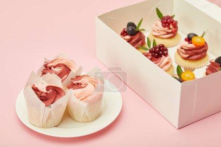 Photo pour Boîte et assiette avec cupcakes sucrés sur la surface rose - image libre de droit