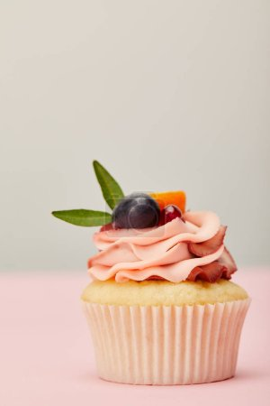 Photo for Tasty cupcake with cream and fruits on pink surface isolated on grey - Royalty Free Image