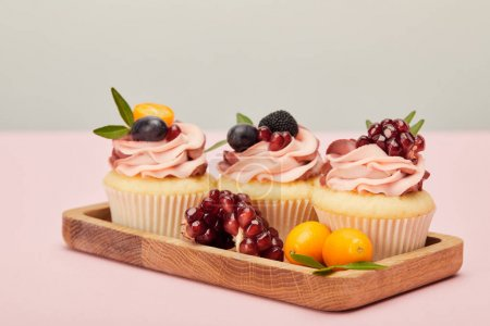 Photo for Wooden tray with sweet cupcakes on pink surface isolated on grey - Royalty Free Image