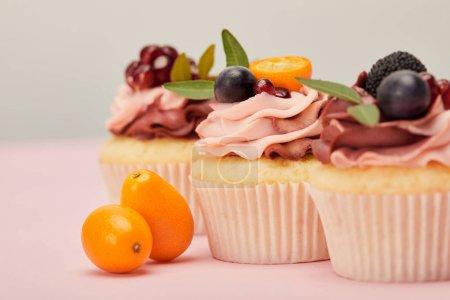 enfoque selectivo de cupcakes con kumquats en la superficie rosa