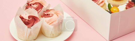 panoramic shot of tasty cupcakes on white plate and in box on pink surface