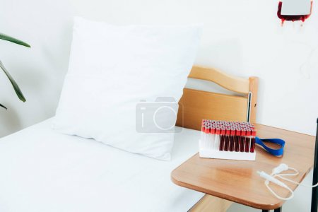 bed, wooden table, test tubes and blood bag in clinic