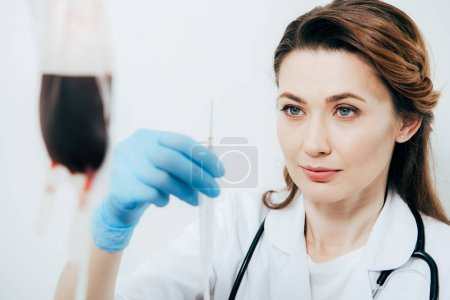 Photo for Doctor in white coat and latex glove holding syringe in hospital - Royalty Free Image