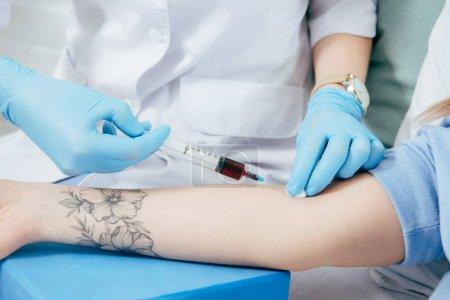 Photo pour Vue recadrée du donneur et du médecin avec seringue obtenant un échantillon de sang - image libre de droit