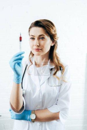 Photo pour Docteur dans la seringue de fixation de gants de latex avec l'échantillon de sang - image libre de droit