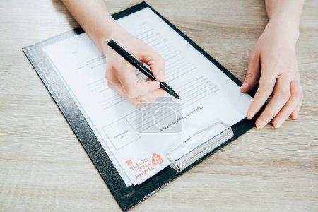 Photo pour Vue recadrée du formulaire d'enregistrement de la signature du donneur sur une surface en bois - image libre de droit