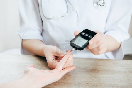 Photo for Cropped view of donor and doctor measuring glucose level with glucometer - Royalty Free Image