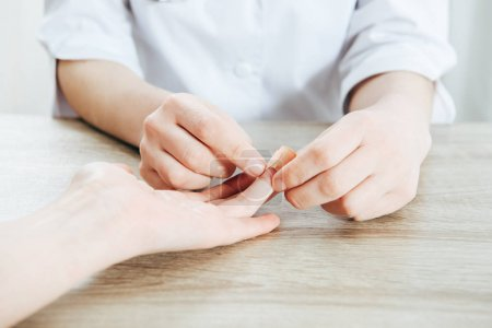 Photo for Partial view of donor and doctor using adhesive bandage - Royalty Free Image