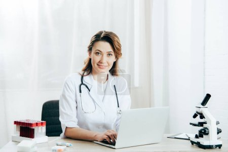 Photo for Doctor in white coat with stethoscope using laptop in clinic - Royalty Free Image