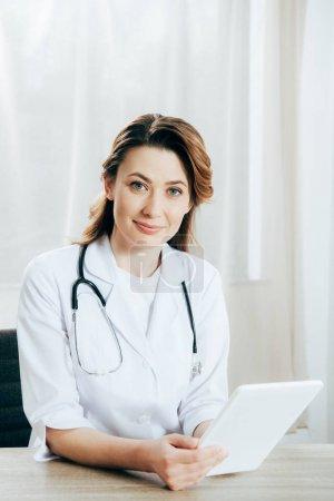 Photo pour Docteur de sourire dans le manteau blanc avec le stéthoscope utilisant la tablette numérique dans la clinique - image libre de droit