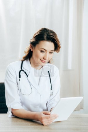 Photo for Smiling doctor in white coat with stethoscope using digital tablet in clinic - Royalty Free Image