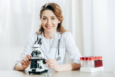 Photo for Doctor in white coat with stethoscope using microscope in clinic - Royalty Free Image