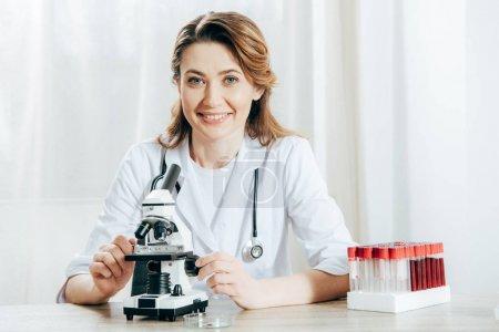 Photo pour Docteur dans le manteau blanc avec le stéthoscope utilisant le microscope dans la clinique - image libre de droit