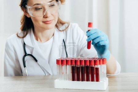 Photo for Concentrated doctor in protective goggles holding test tube with blood - Royalty Free Image