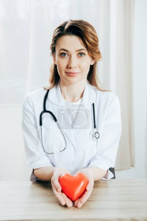 Photo for Smiling doctor in white coat with stethoscope holding plastic heart - Royalty Free Image