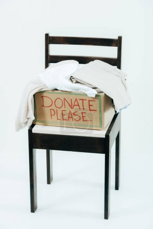 Photo for Cardboard box with donated clothes on wooden chair on white - Royalty Free Image