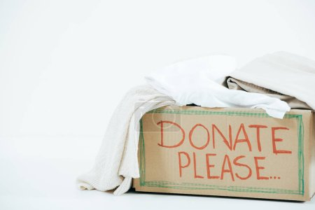 Photo for Cardboard box with inscription and donated clothes on white - Royalty Free Image
