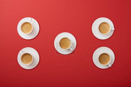 Photo for Top view of white cups with coffee on saucers on red background - Royalty Free Image