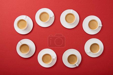 Photo pour Vue de dessus des tasses blanches avec café savoureux sur des soucoupes sur fond rouge - image libre de droit