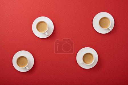 Photo pour Vue de dessus des tasses blanches avec délicieux café sur soucoupes sur fond rouge - image libre de droit