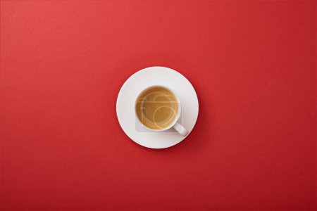 Photo for Top view of white cup with coffee on saucer on red background - Royalty Free Image