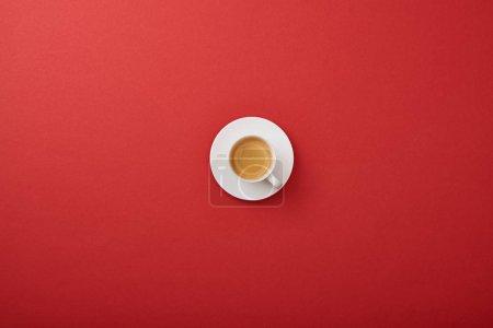 Photo pour Vue supérieure de tasse blanche avec le café frais sur la soucoupe sur le fond rouge - image libre de droit