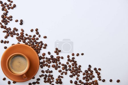 Photo for Top view of delicious coffee in cup near scattered beans on white background with copy space - Royalty Free Image