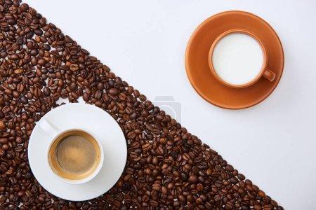 Photo pour Vue supérieure du café délicieux dans la tasse parmi les haricots torréfiés près de tasse de lait sur le fond blanc - image libre de droit