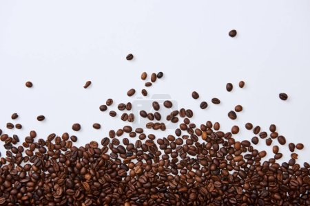 Photo for Top view of scattered brown roasted beans on white background - Royalty Free Image