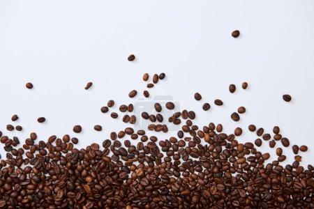 Photo pour Vue supérieure des haricots rôtis bruns dispersés sur le fond blanc - image libre de droit