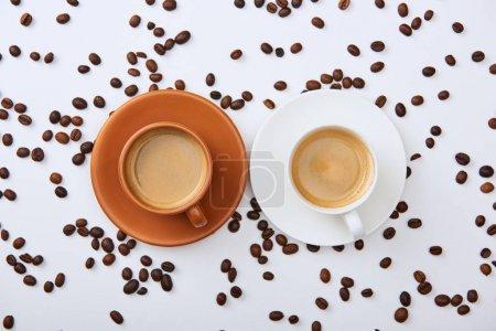 Photo pour Vue du haut du café dans les tasses blanches et brunes sur des soucoupes près des haricots torréfiés dispersés - image libre de droit
