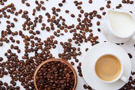 Photo pour Vue du dessus du café dans la tasse sur la soucoupe près des haricots rôtis dispersés, bol en bois et cruche à lait - image libre de droit