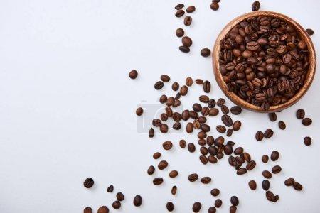 Photo pour Vue supérieure des haricots torréfiés de café dans le bol en bois sur le fond blanc - image libre de droit